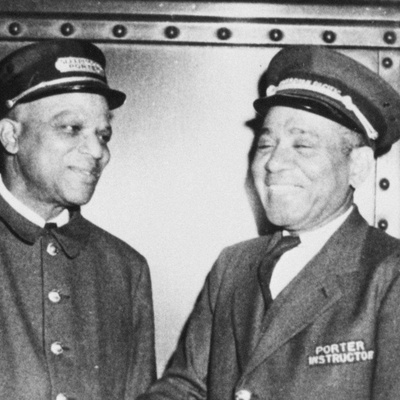 A black and white photo of four men in train porter uniforms. All of the men are smiling, and the two men in the middle appear to be shaking hands.