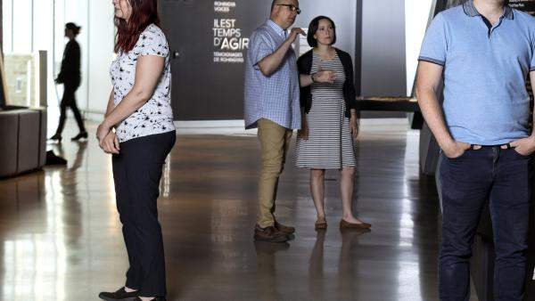 Small groups of people stand in a Museum exhibition space and talk to one another.