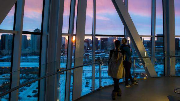 Two people gaze out a tall glass window at a sunset over a cityscape.