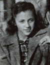 A girl wearing a coat sits on a bench in a black and white photo.