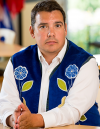 A man wearing a blue vest with flower beadwork, seated with his hands resting on a table.
