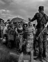 A soldier with a rifle on his back blocks a group of Rohingya before they cross a makeshift bridge. His left hand is raised, gesturing for them to stop.