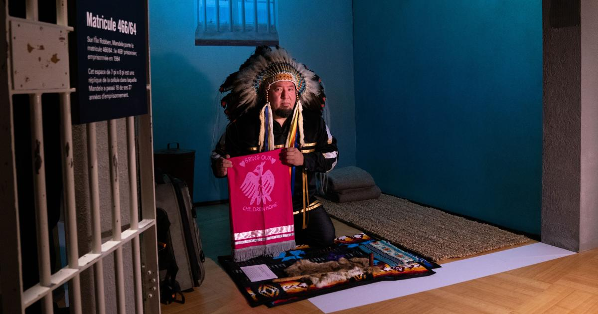 "An indigenous man wearing ceremonial regalia kneels inside a replica of a prison cell. He is presenting a textile banner with a graphic image of a bird and the words ""bring our children home""."