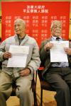 Two old men sit holding papers in front of them.Immigration.