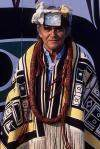 Bill Cranmer, an older man with gray hair, stands facing the camera. He is wearing a fringed blanket over his shoulders that decorated with geometric designs. He is also wearing fur hat with a shiny square metal centrepiece and a large necklace made out of a thick cord.